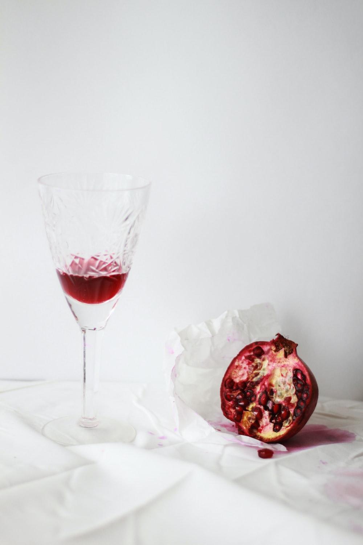 clear cut wine glass beside pomegranate