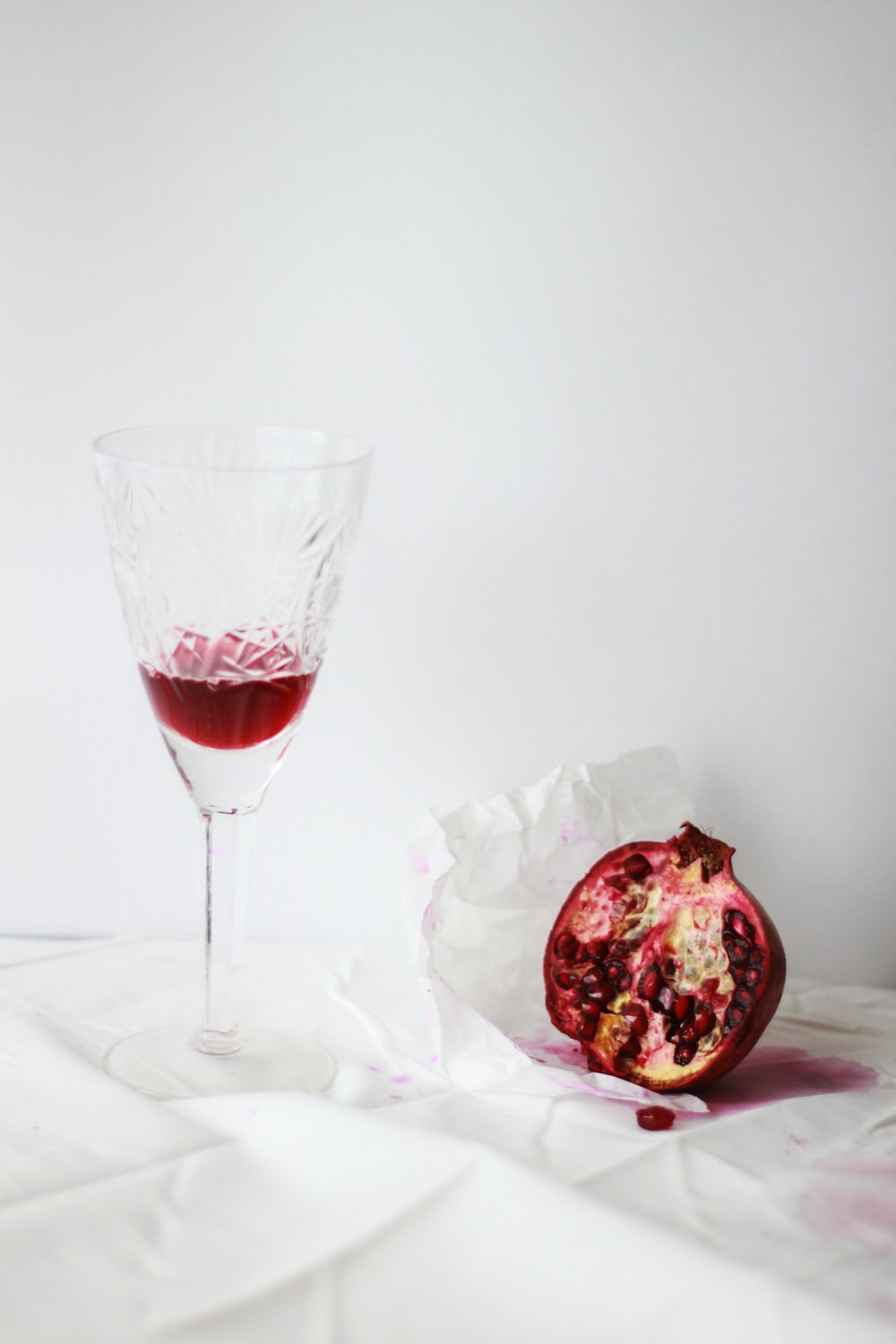 clear cut wine glass beside pomegranate