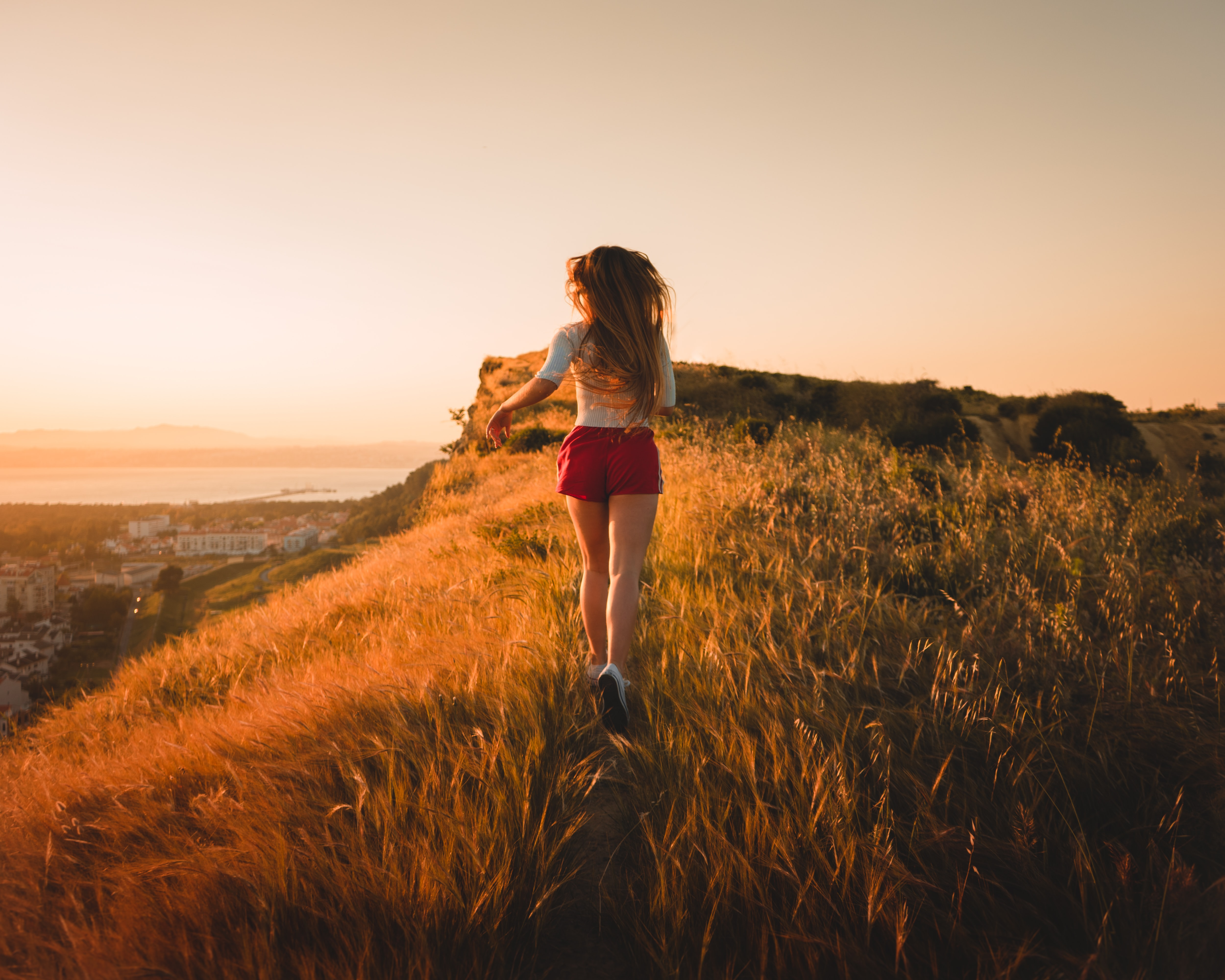 woman running in grass field during sunset