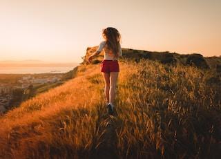 woman running in grass field during sunset
