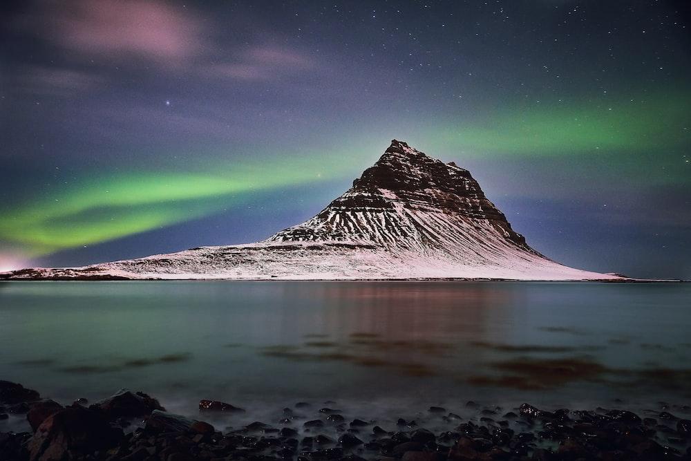 snow capped mountain under aurora