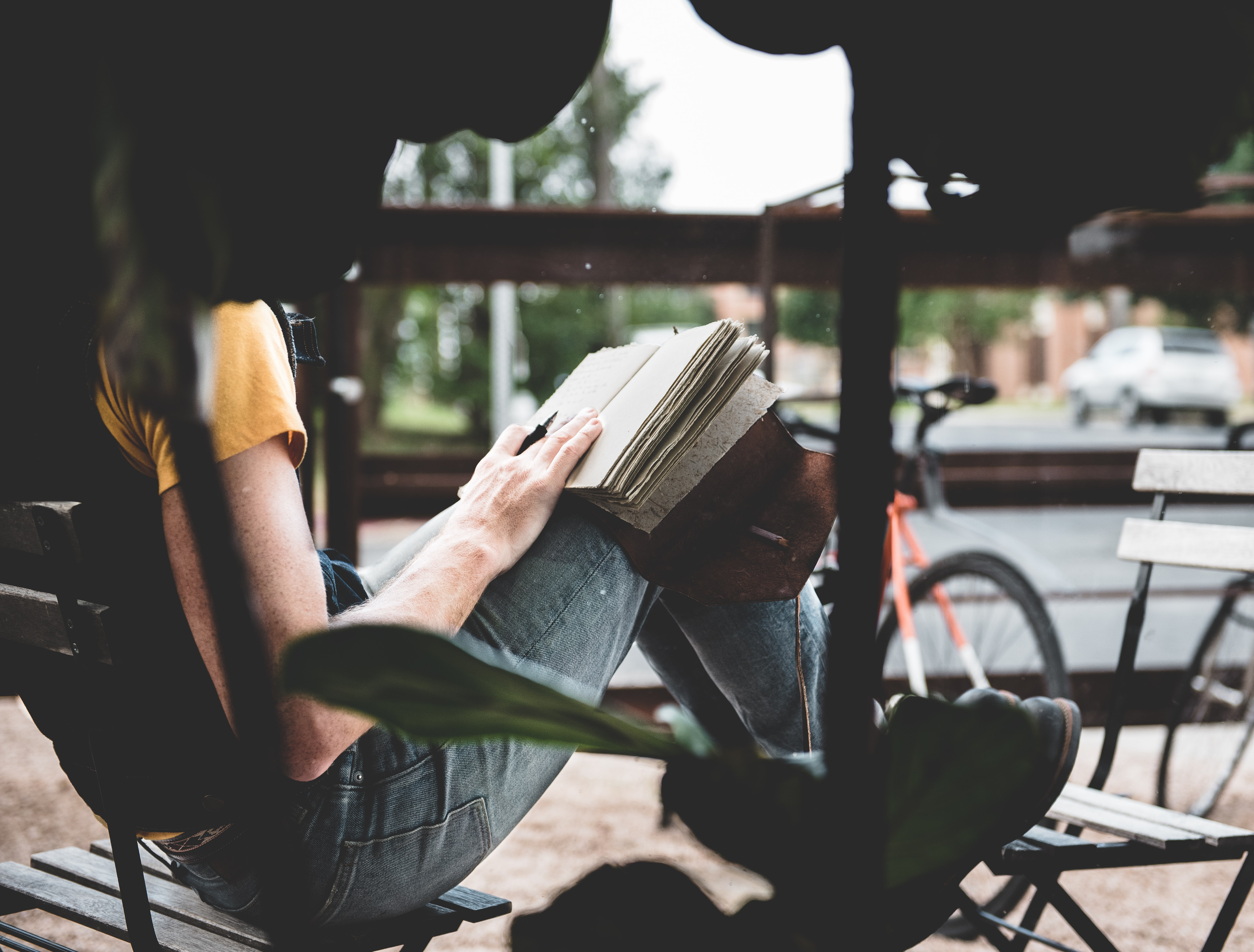 person sitting on wooden chair reading a book
