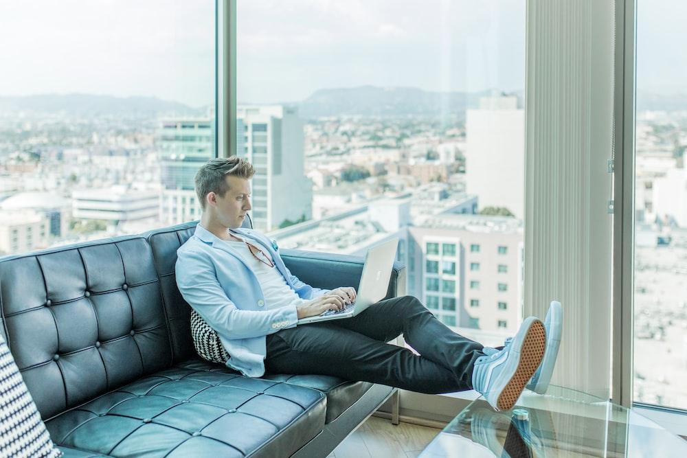 man sitting on sofa while using laptop