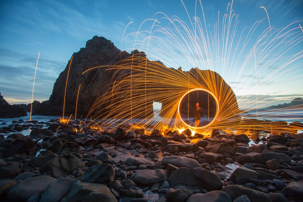 person standing on seashore steel wool photography