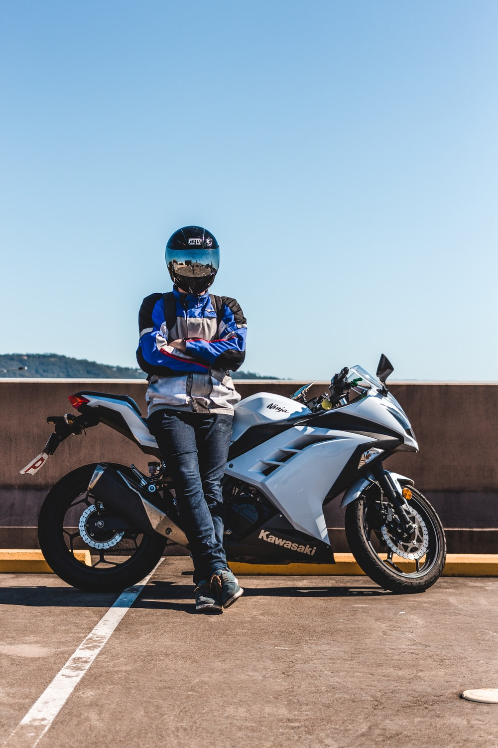 person wearing helmet standing and leaning on Kawasaki sports bike during daytime