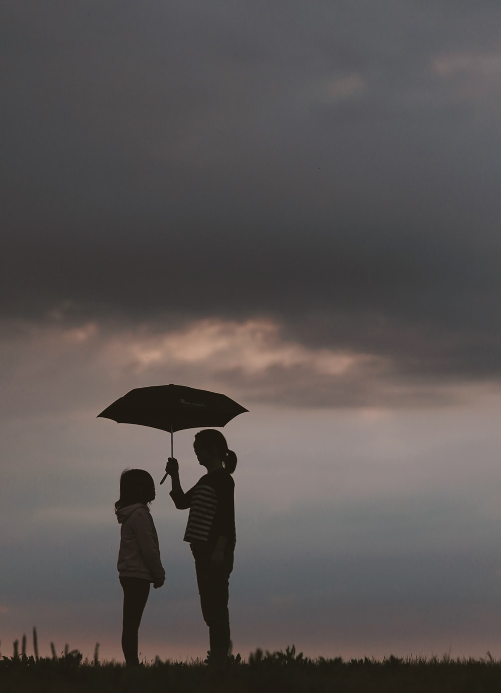 silhouette of woman holding umbrella standing in front of girl on hill during night time