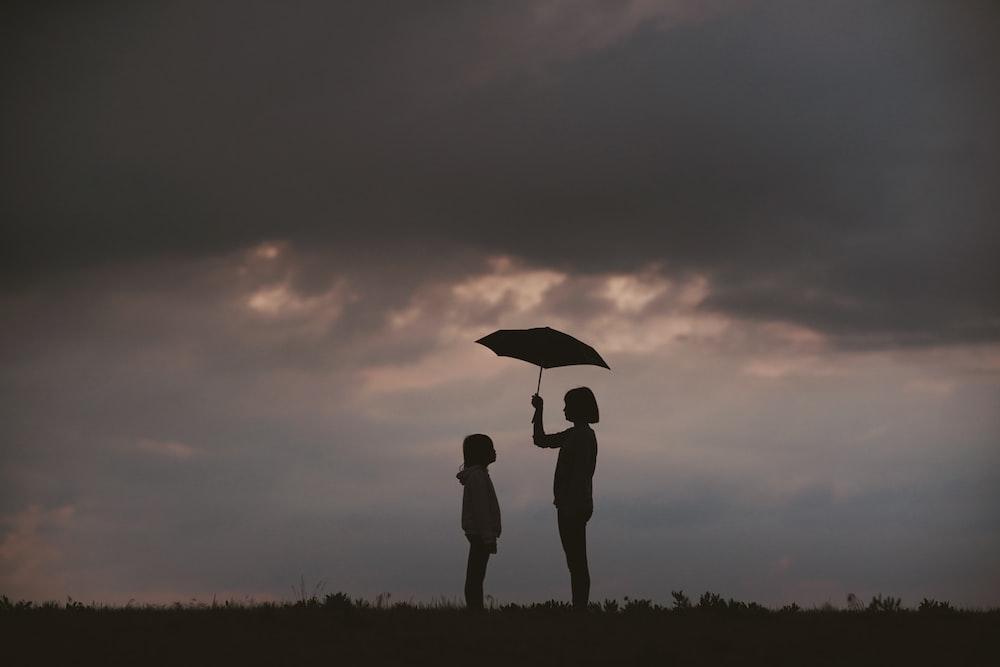 girl holding umbrella on grass field