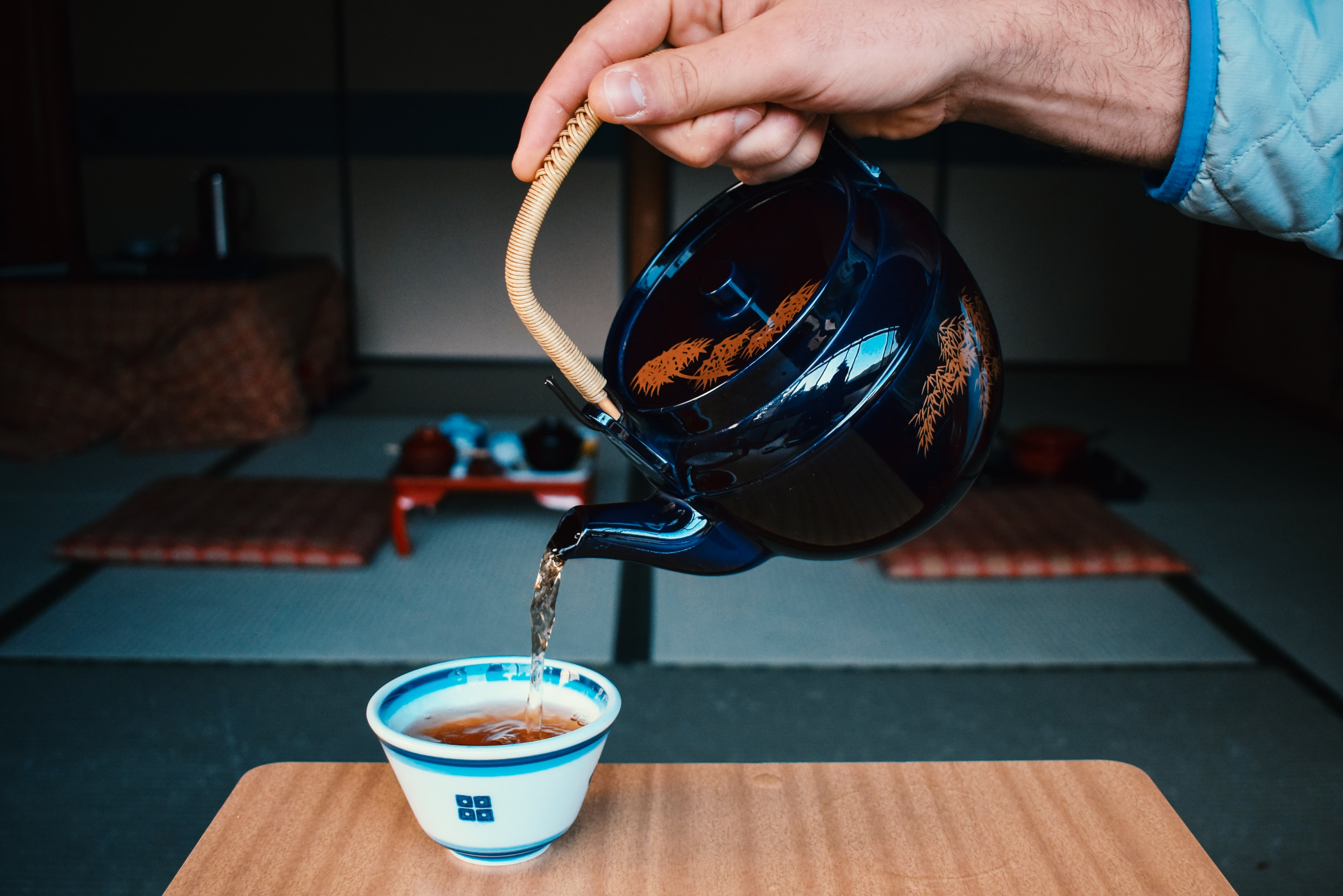 person pouring tea on cup
