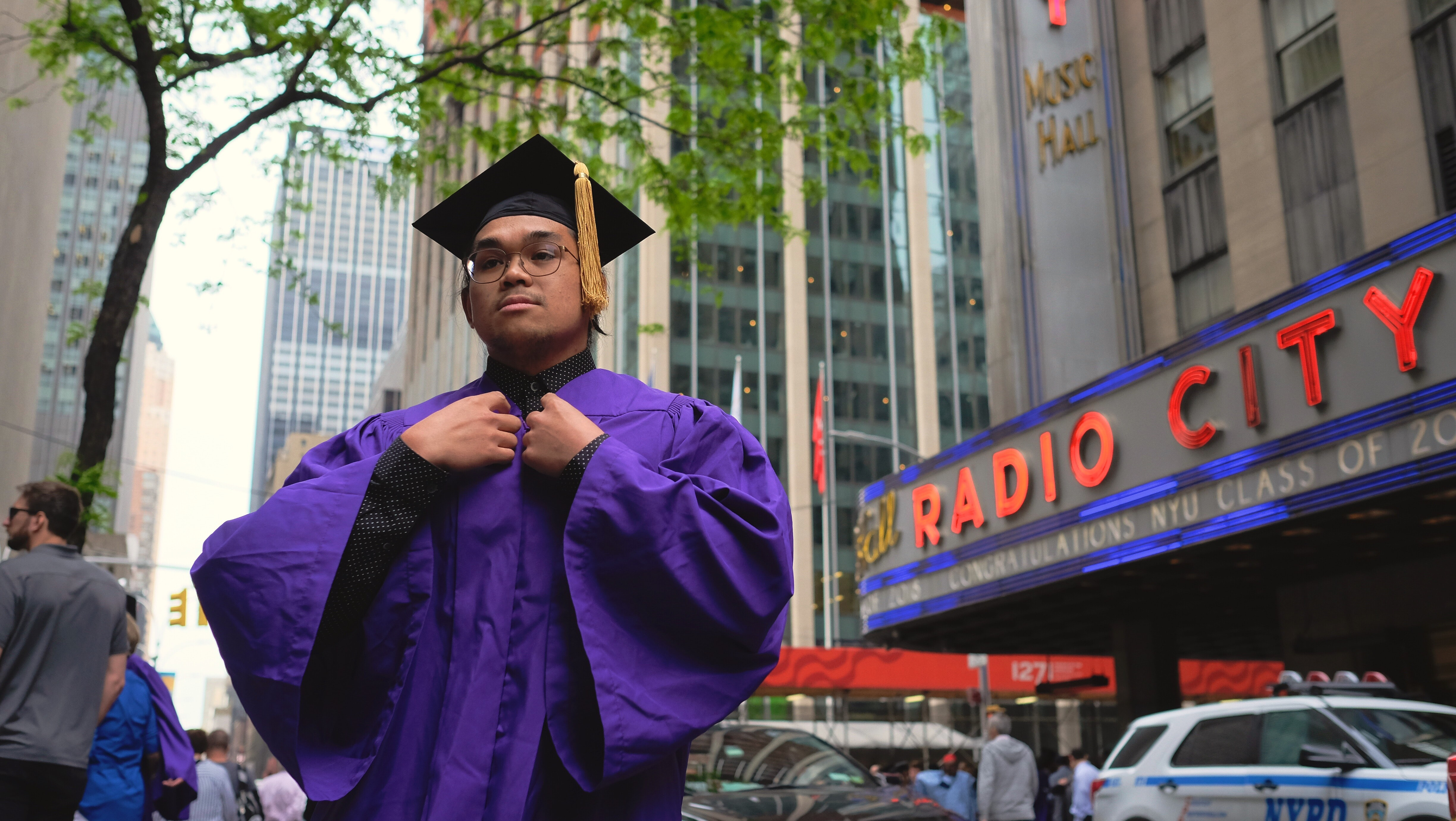 man wearing purple and black educational gown standing near building