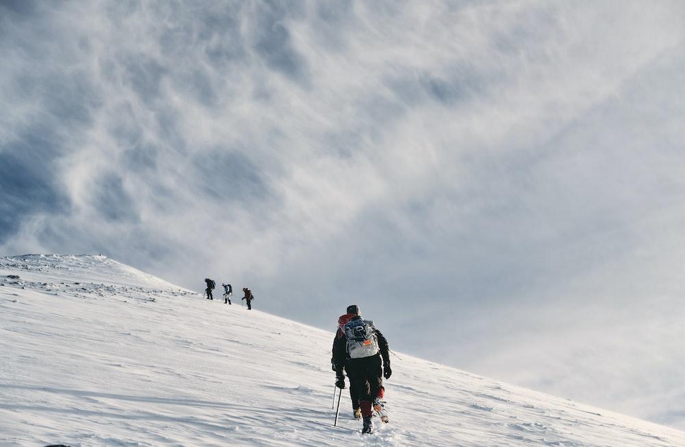men climbing snow covered mountain