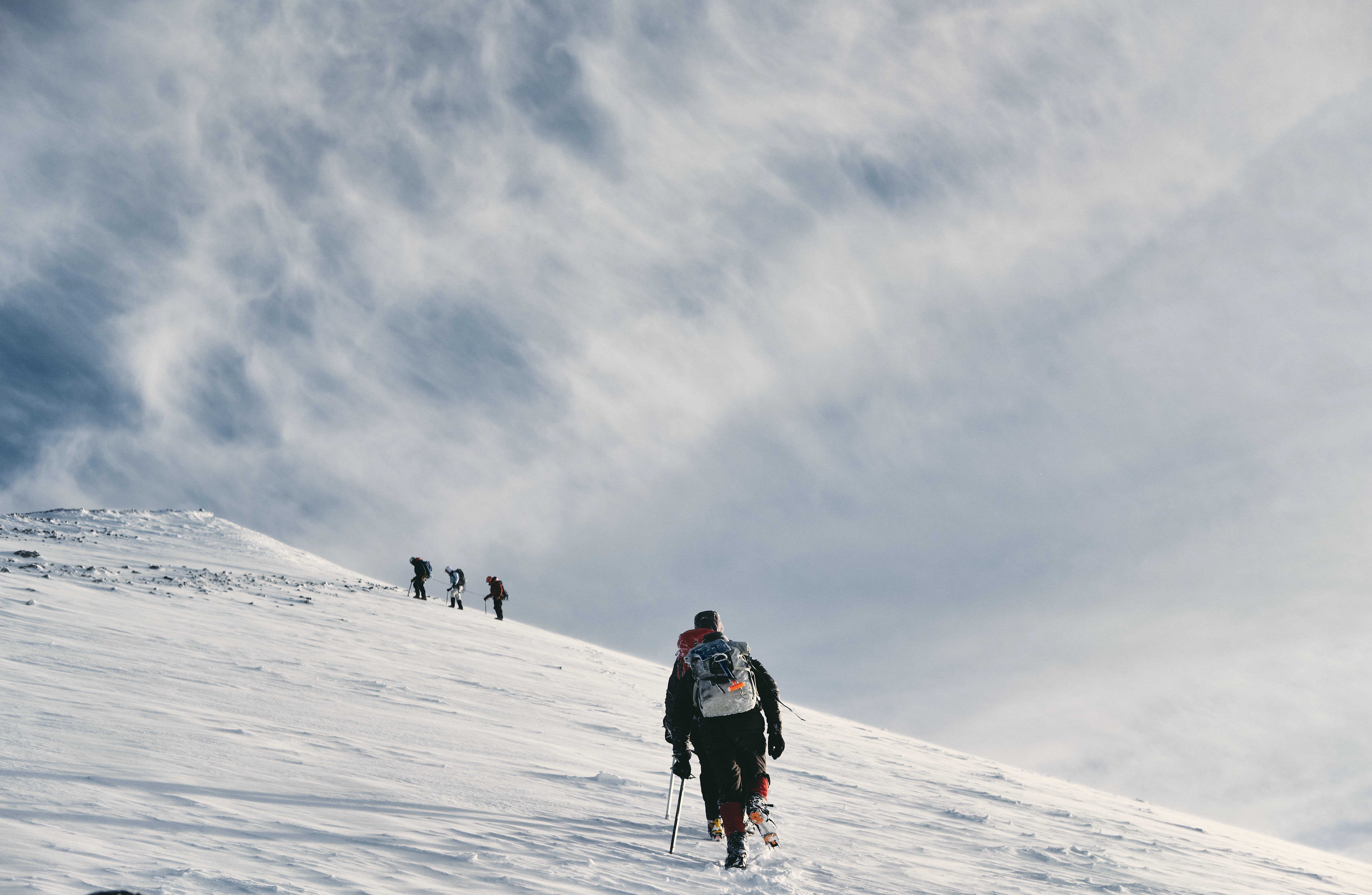 men climbing snow covered mountain