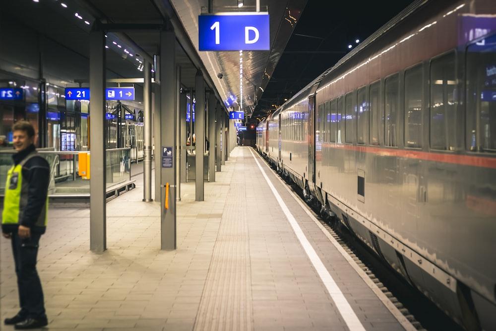 man standing near train inside train station