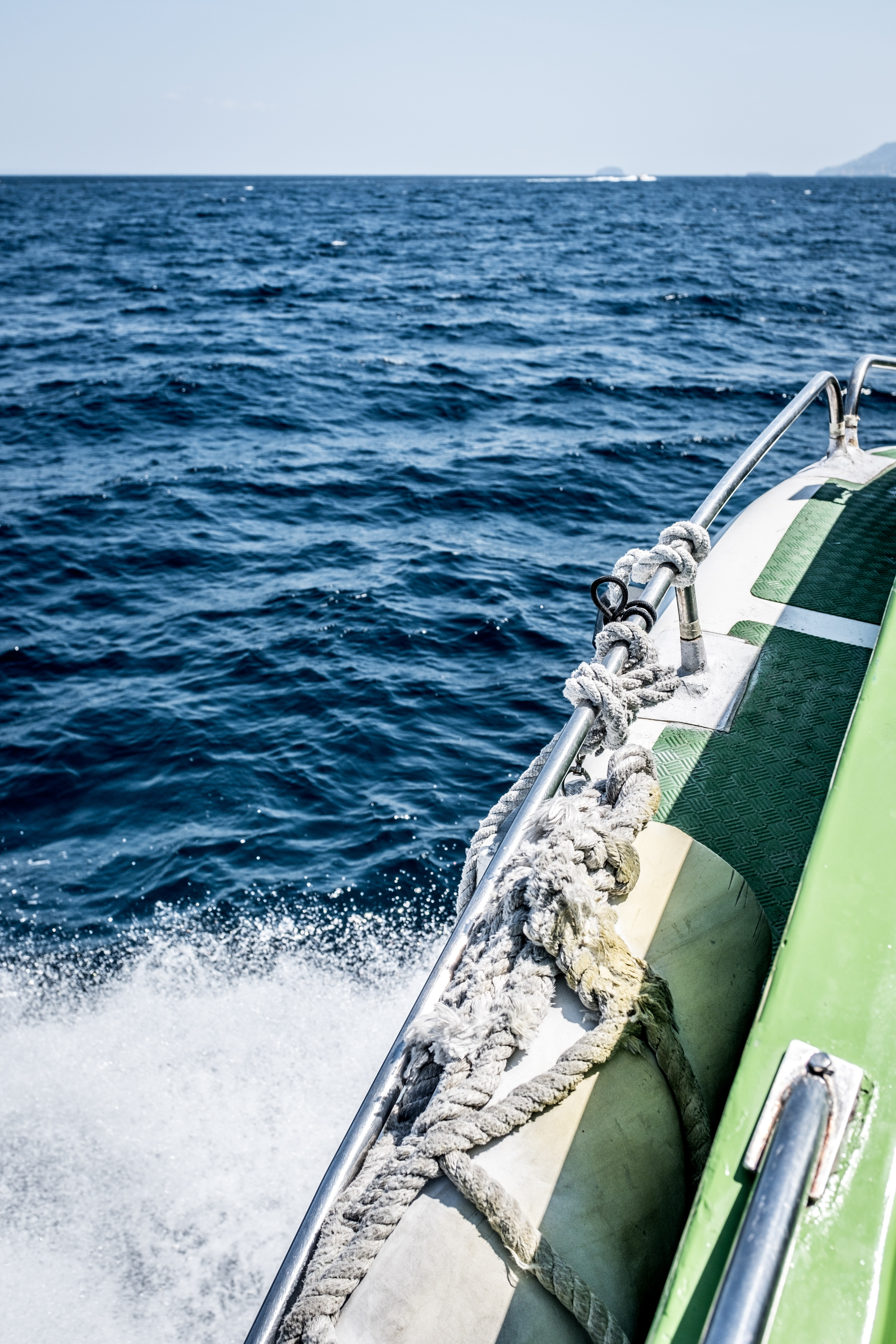 green and white boat sailing on ocean
