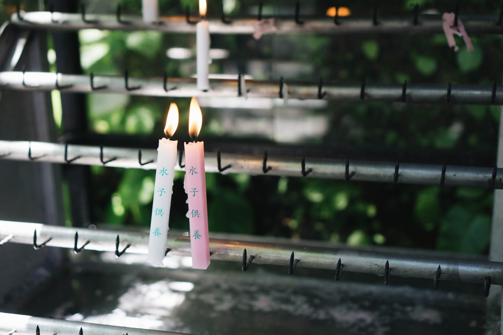 two lighted pink and white candlesticks