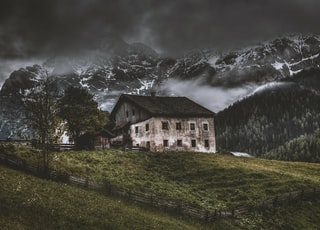 house on top of hill near mountain alps