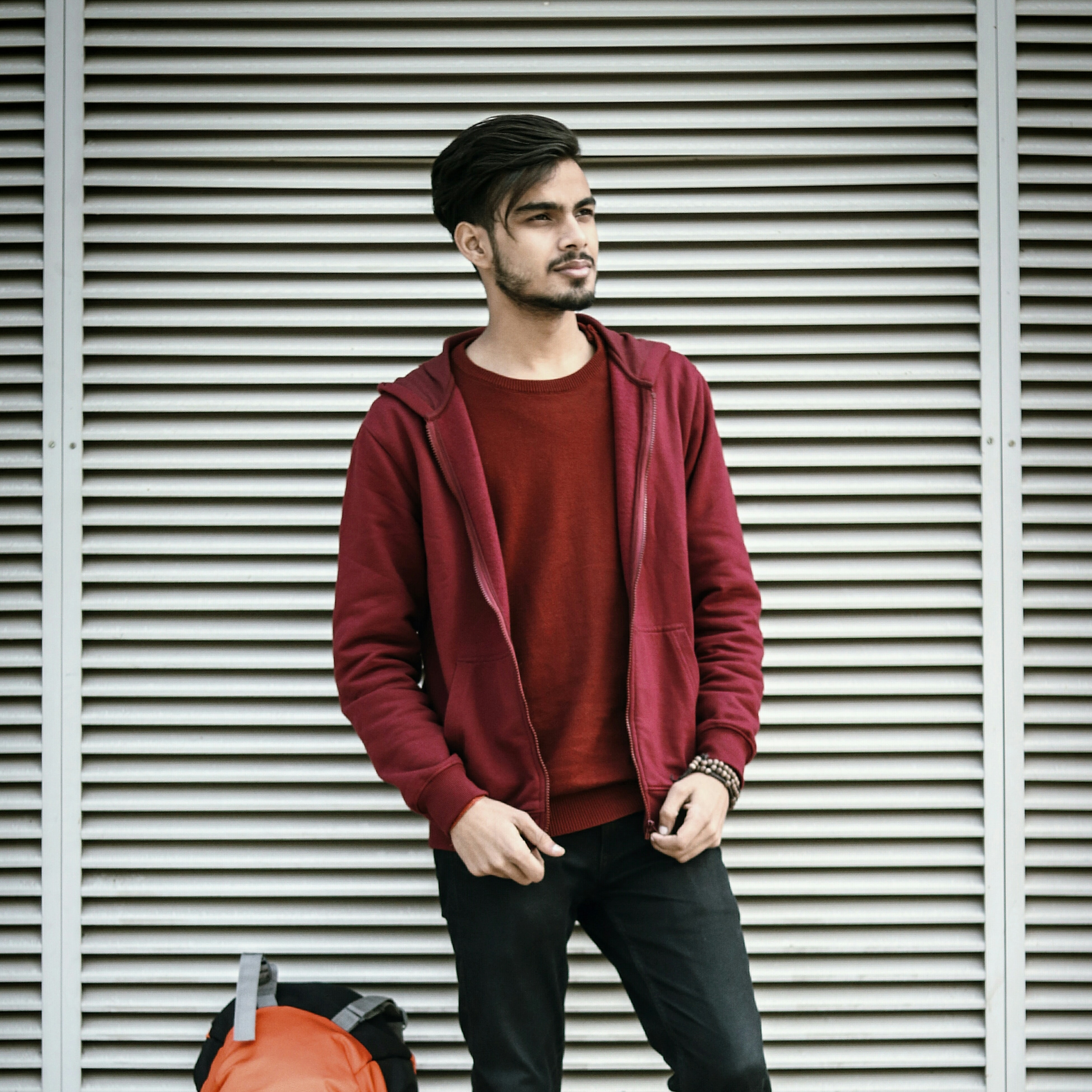 man in red jacket standing beside backpack