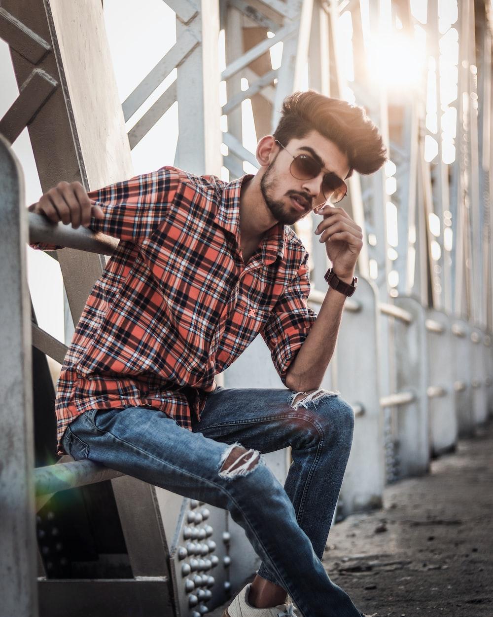 man sitting on railing while wearing sunglasses