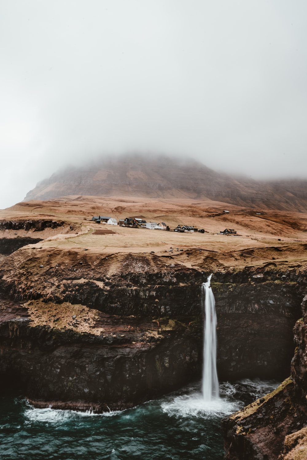 brown mountain with waterfalls under gray cloudy sky