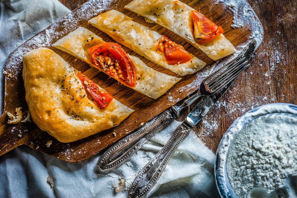 photo of bread with tomato on wooden board beside spoon and knife