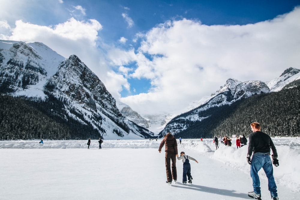 people wearing ice skates with mountain at the distance