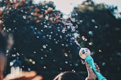 person's hand holding bubble toy create teams background