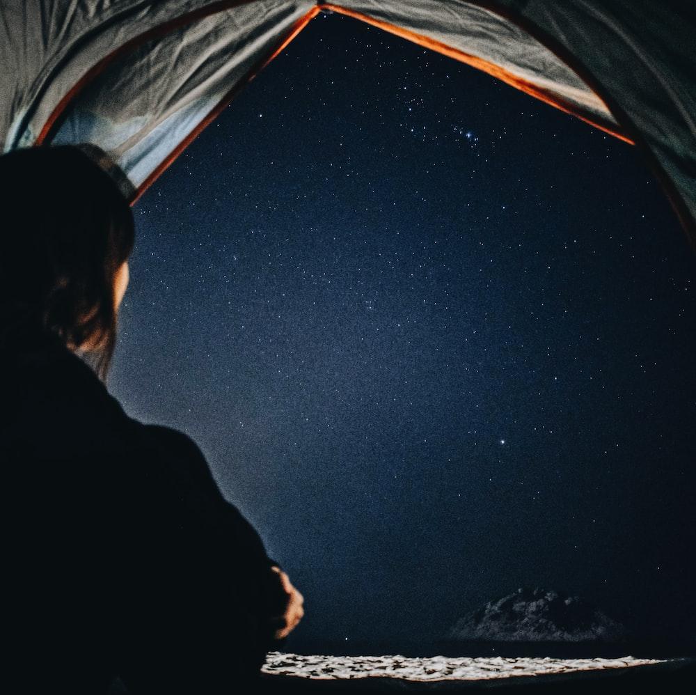 woman staring at stars at sky at night