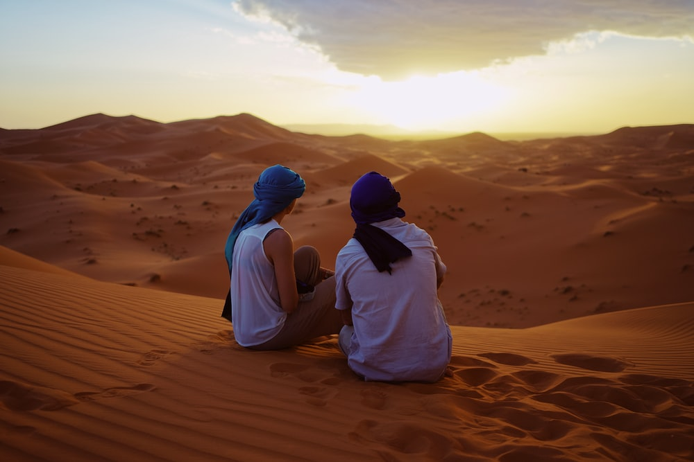 two men sitting on sand dunes