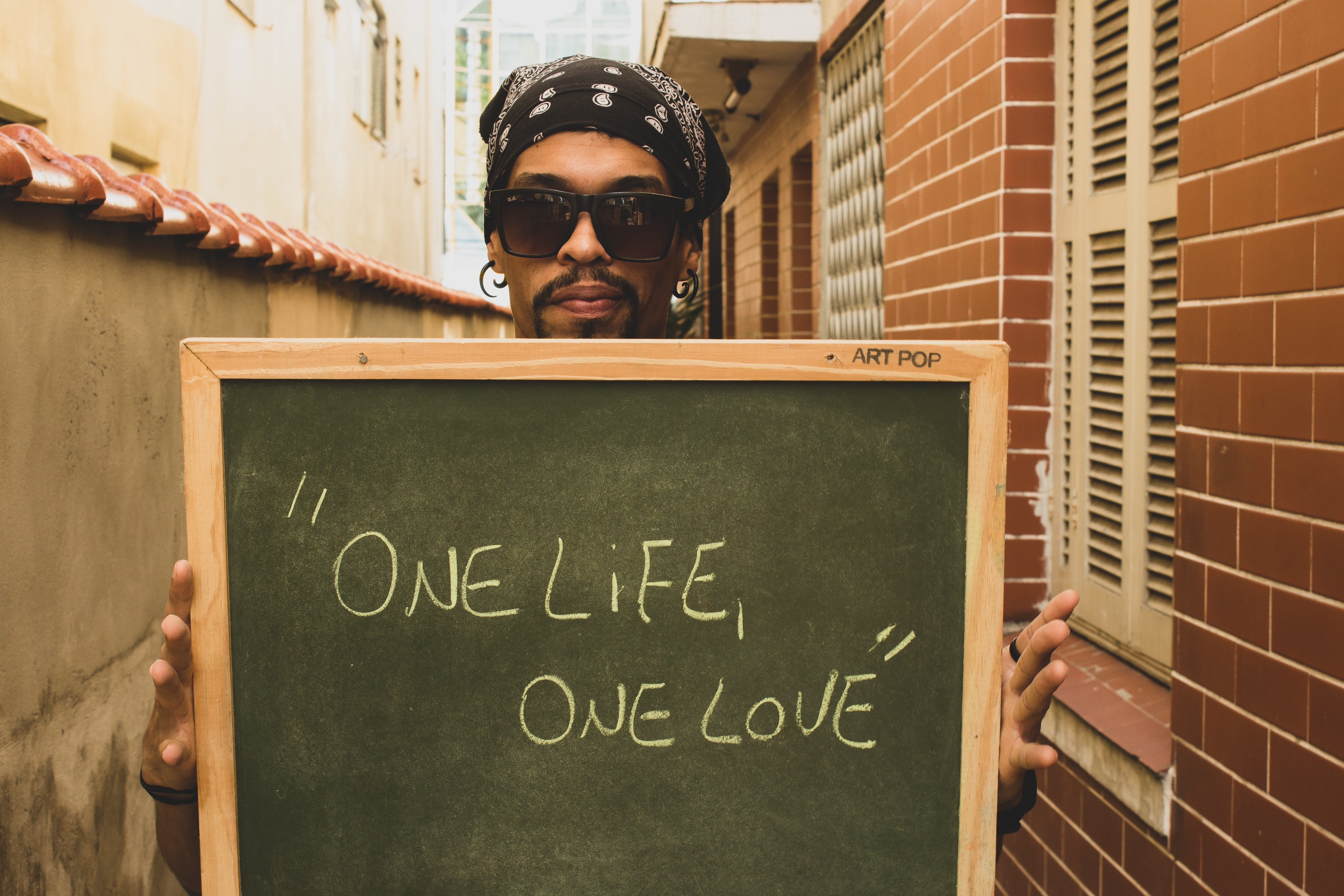man holding one life one love board