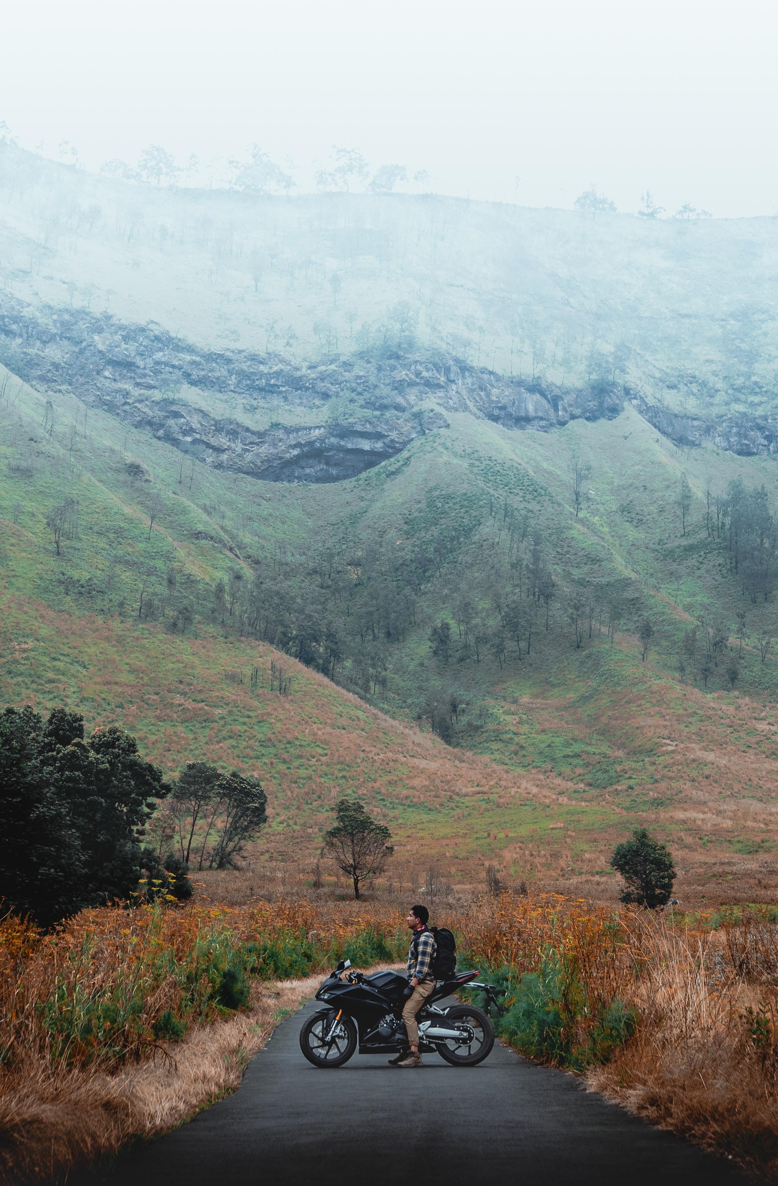 man riding on motorcycle near mountain