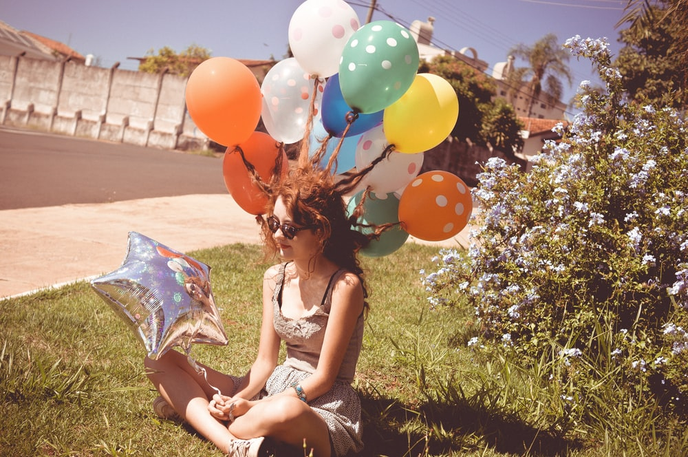 woman sitting on green grass while holding balloons