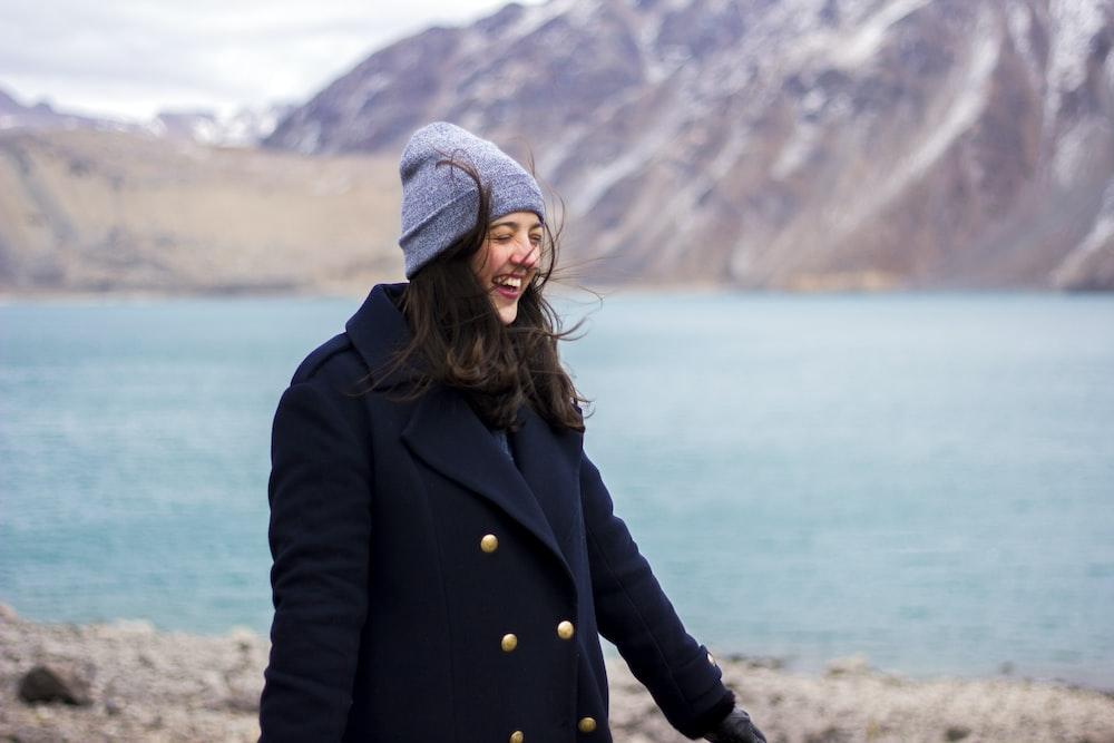 woman wearing coat near shore