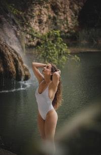 woman wearing white swimsuit standing near body of water