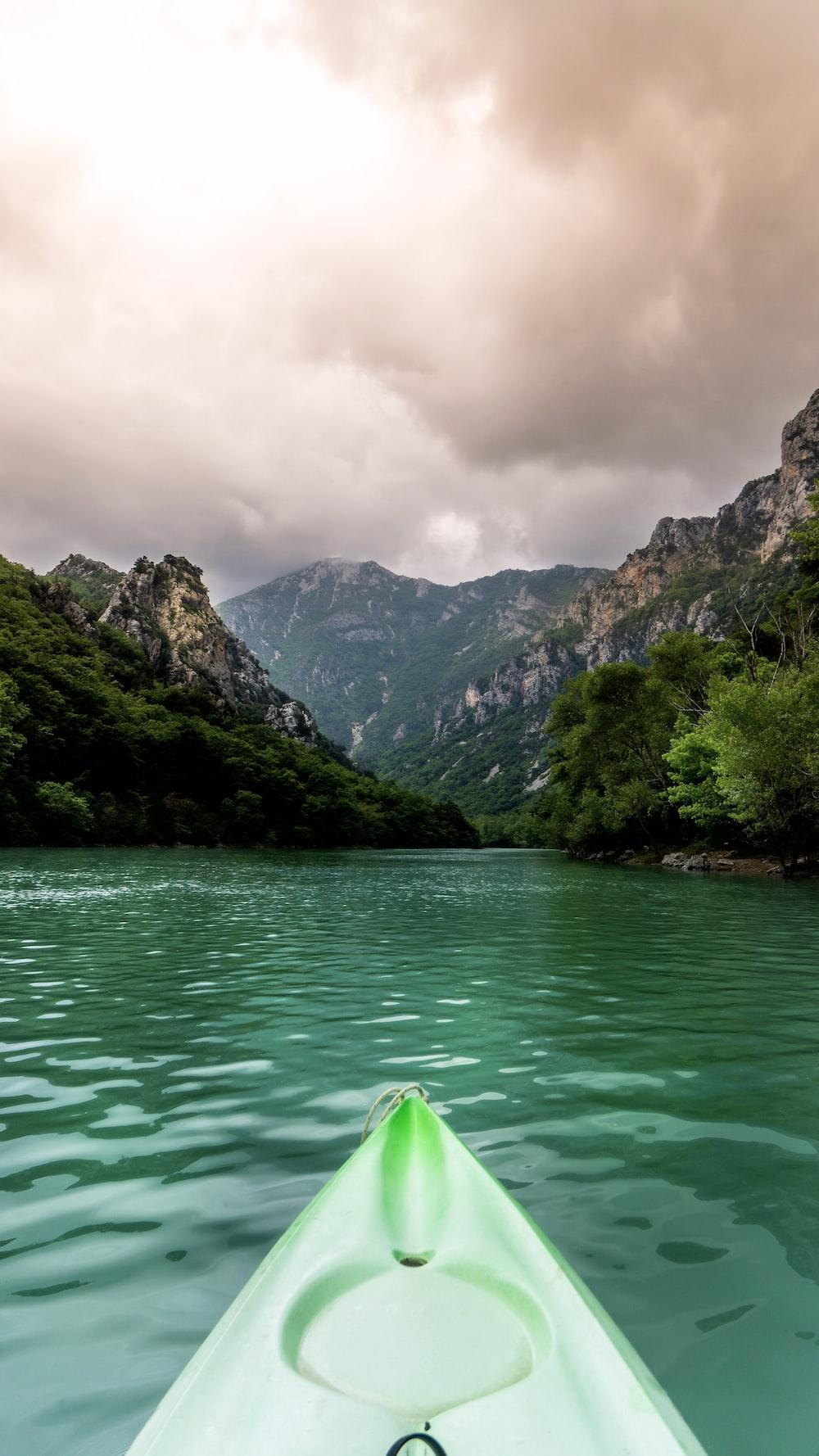 green kayak sailing near grass covered mountains during daytime
