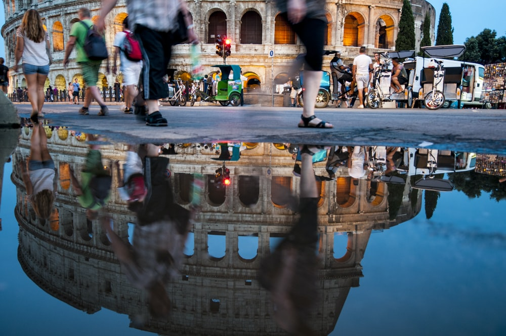 people walking beside The Colosseum, Rome at blue hour
