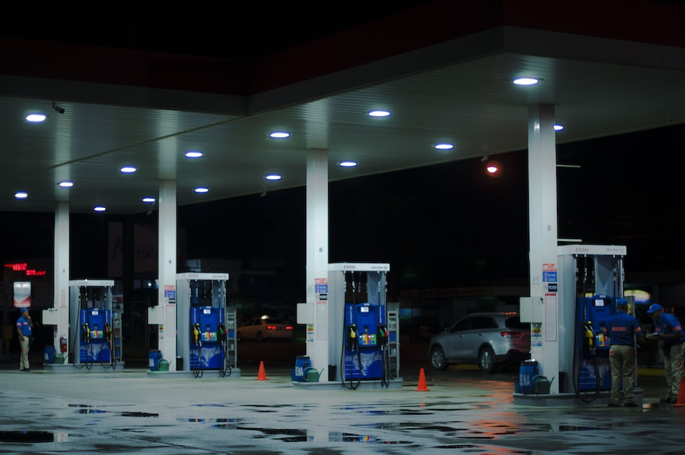 person taking a photo of blue and white gasoline station