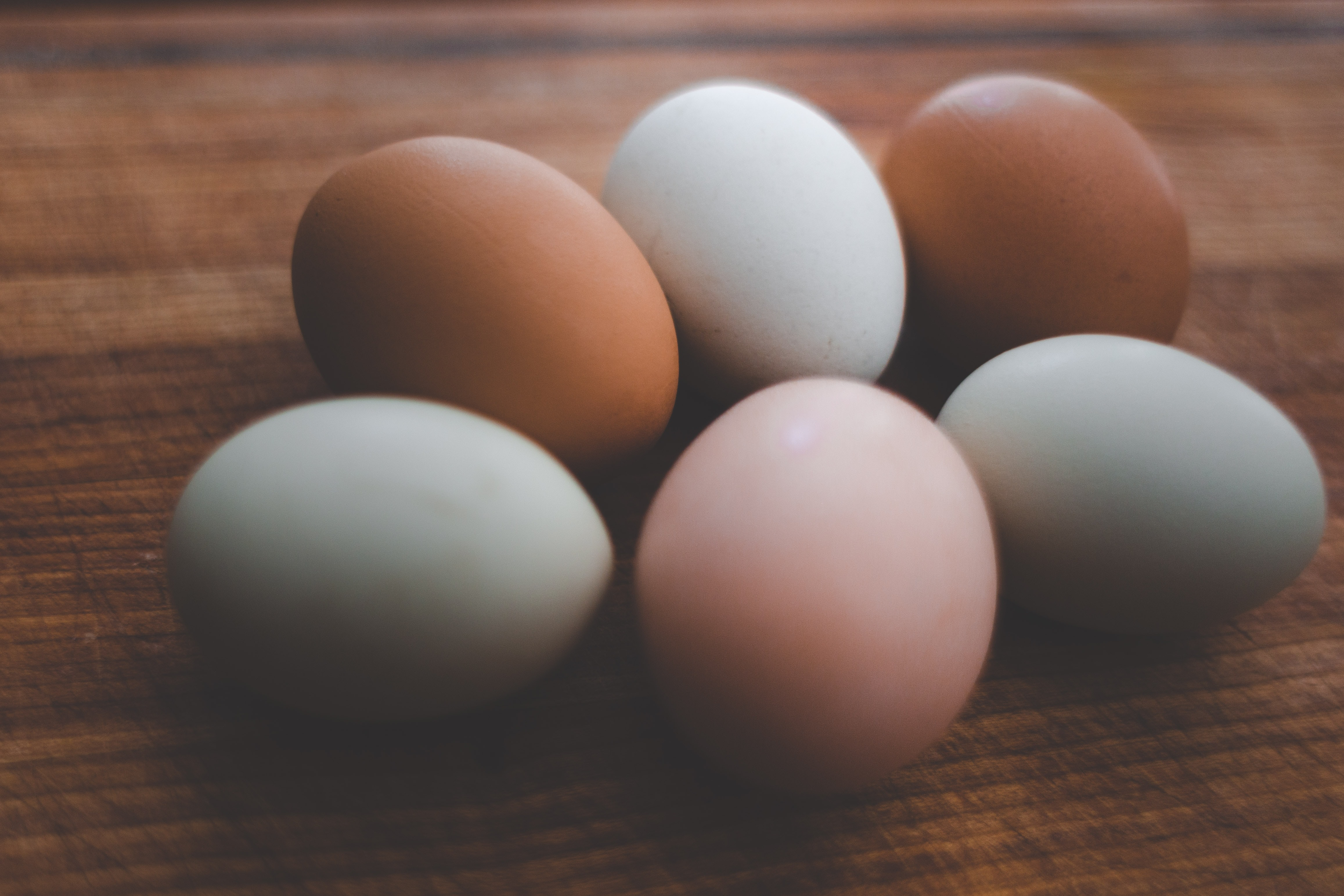 six brown and white egg on brown wooden surface