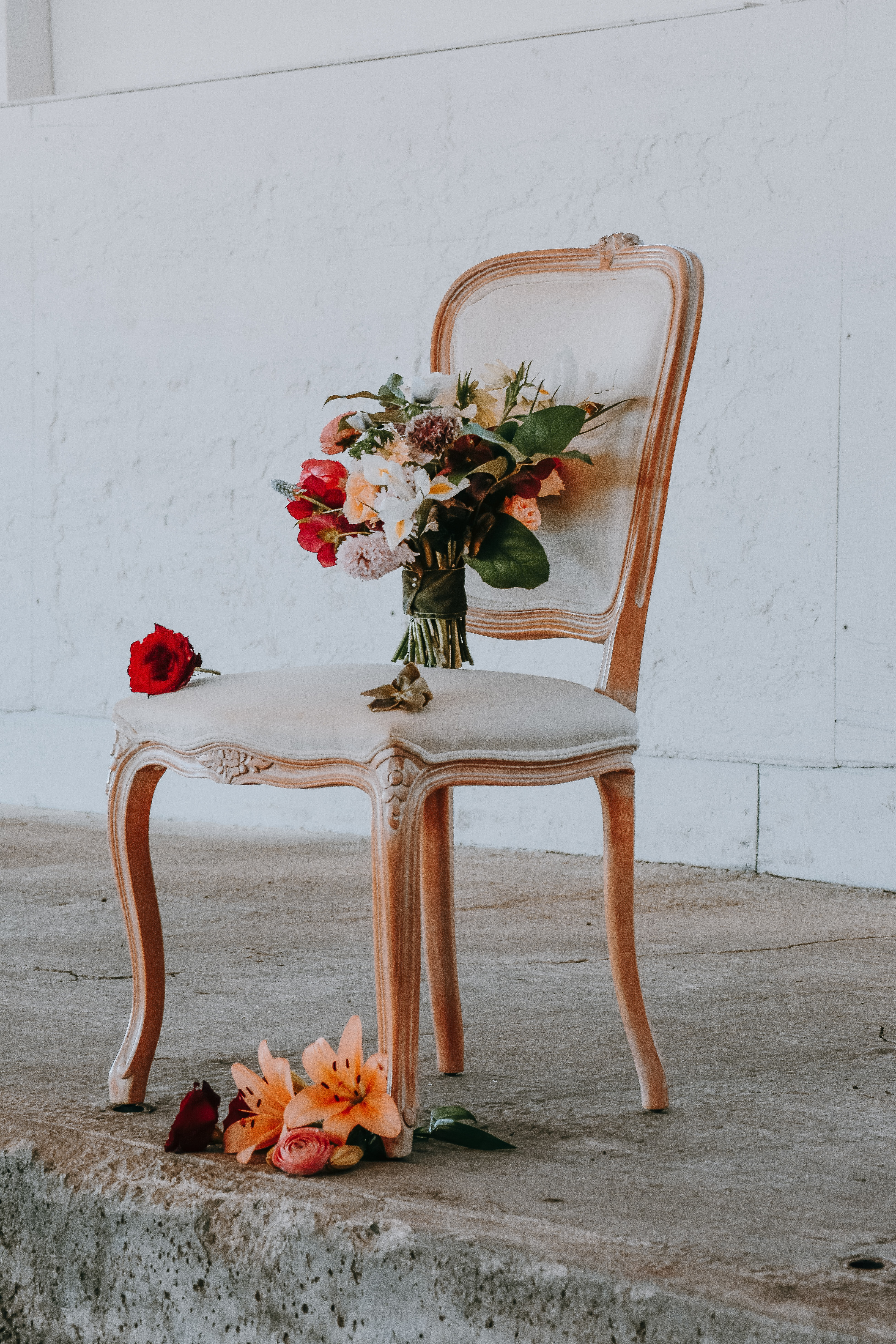 assorted-color flowers on brown wooden framed beige padded chair near wall