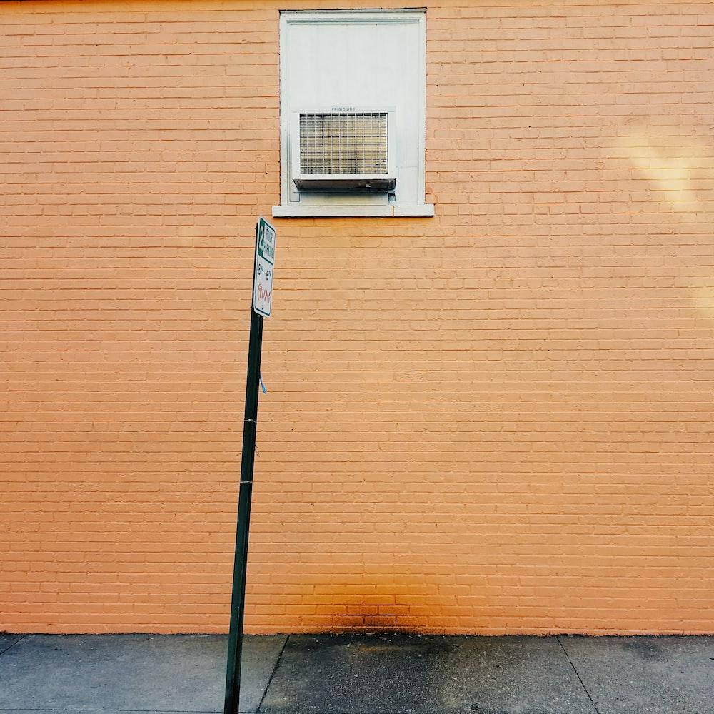 signage near brown brick wall