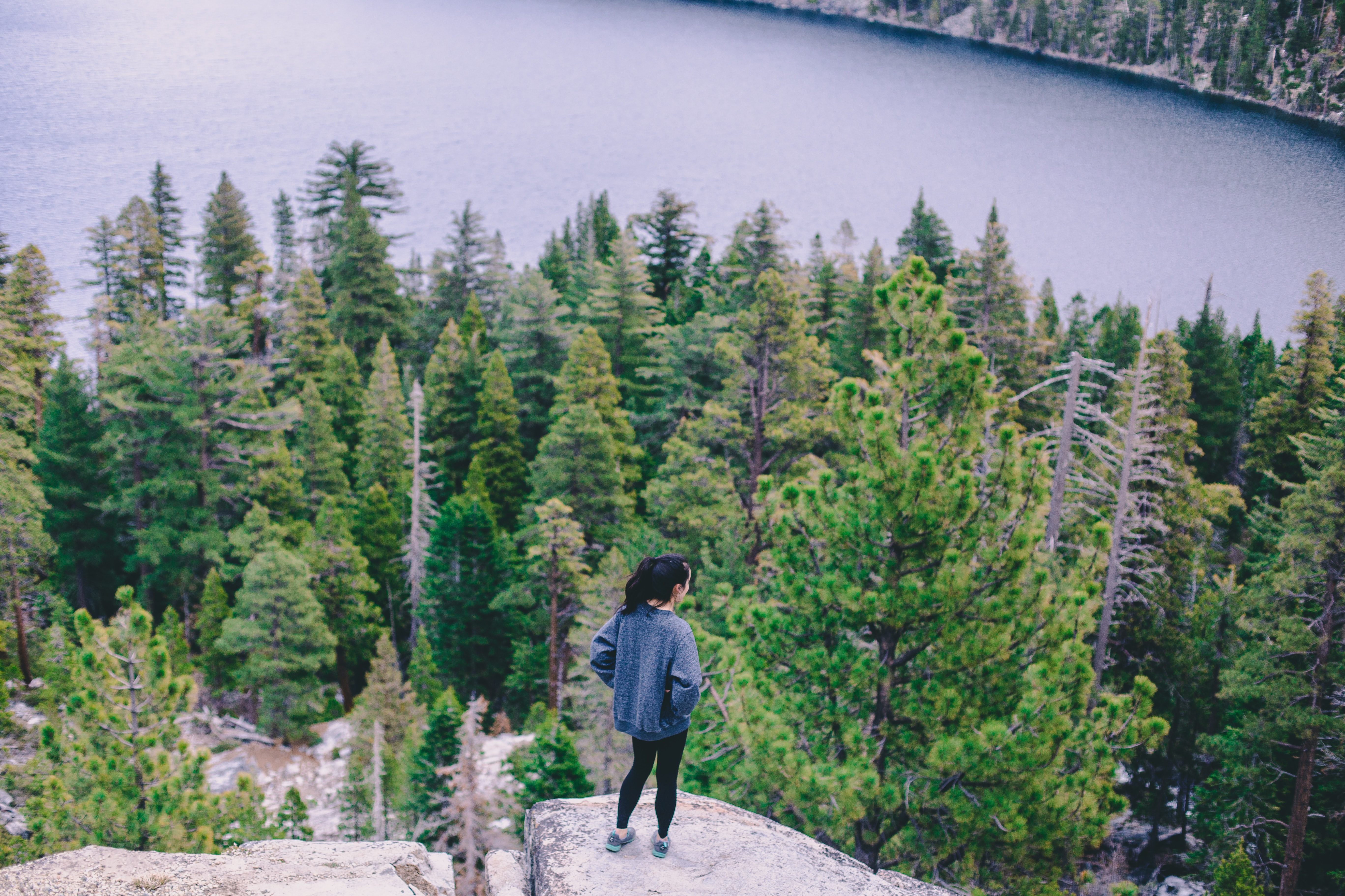 woman standing on cliff above forest and lake