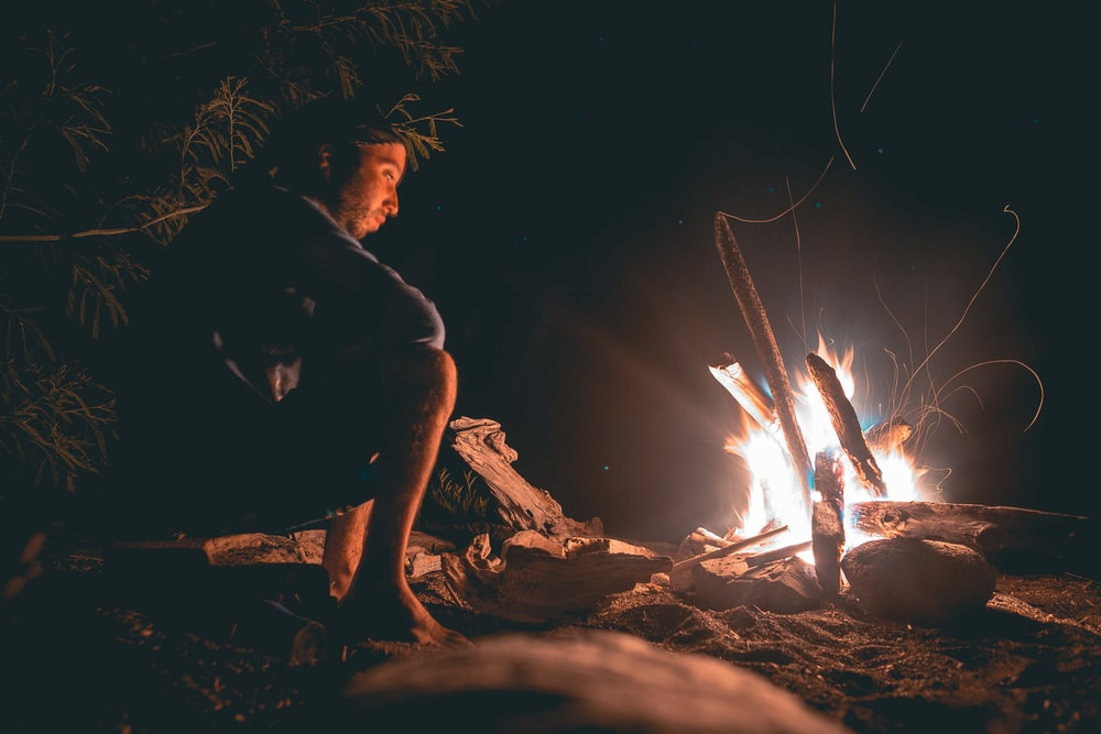 man seating beside fire