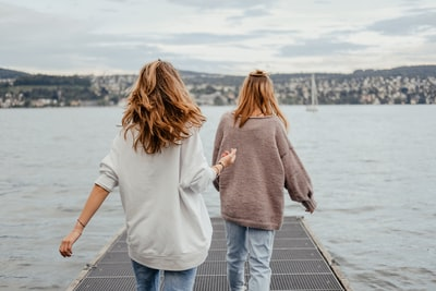 two women standing on dock front of sea at daytime lifestyle teams background