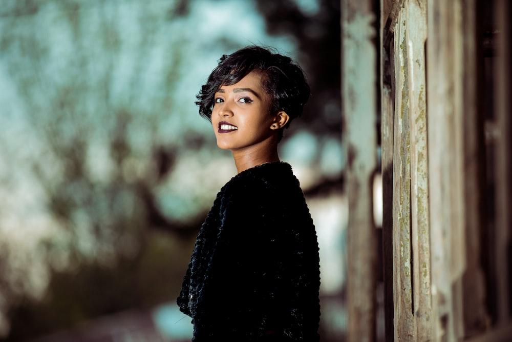 woman wearing black coat standing near brown wall