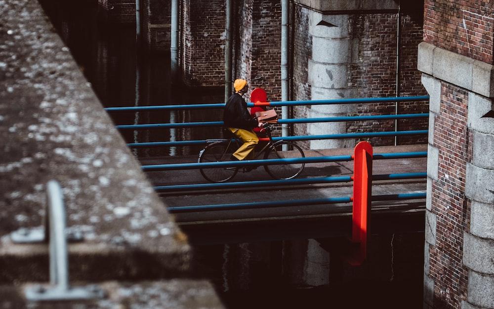 man riding bicycle on gray concrete bridge during daytime