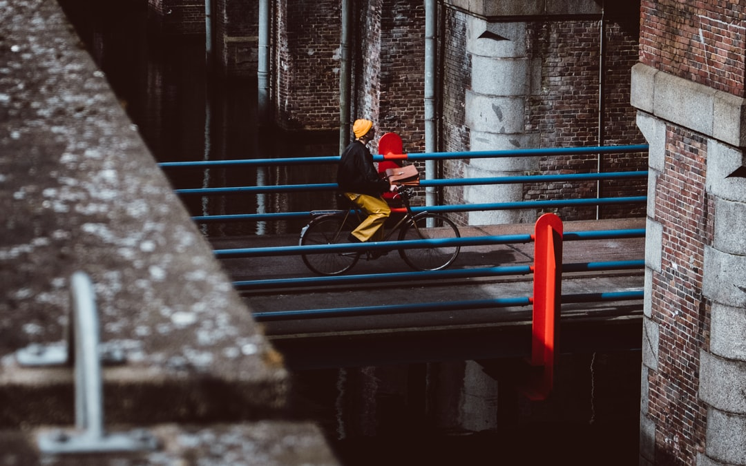 This guy was really standing out with his yellow jeans and orange beanie. I also like the contrast with the blue and red bridge. Took this in Amsterdam a while ago.