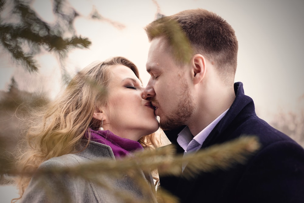 man and woman kissing near green leafed tree