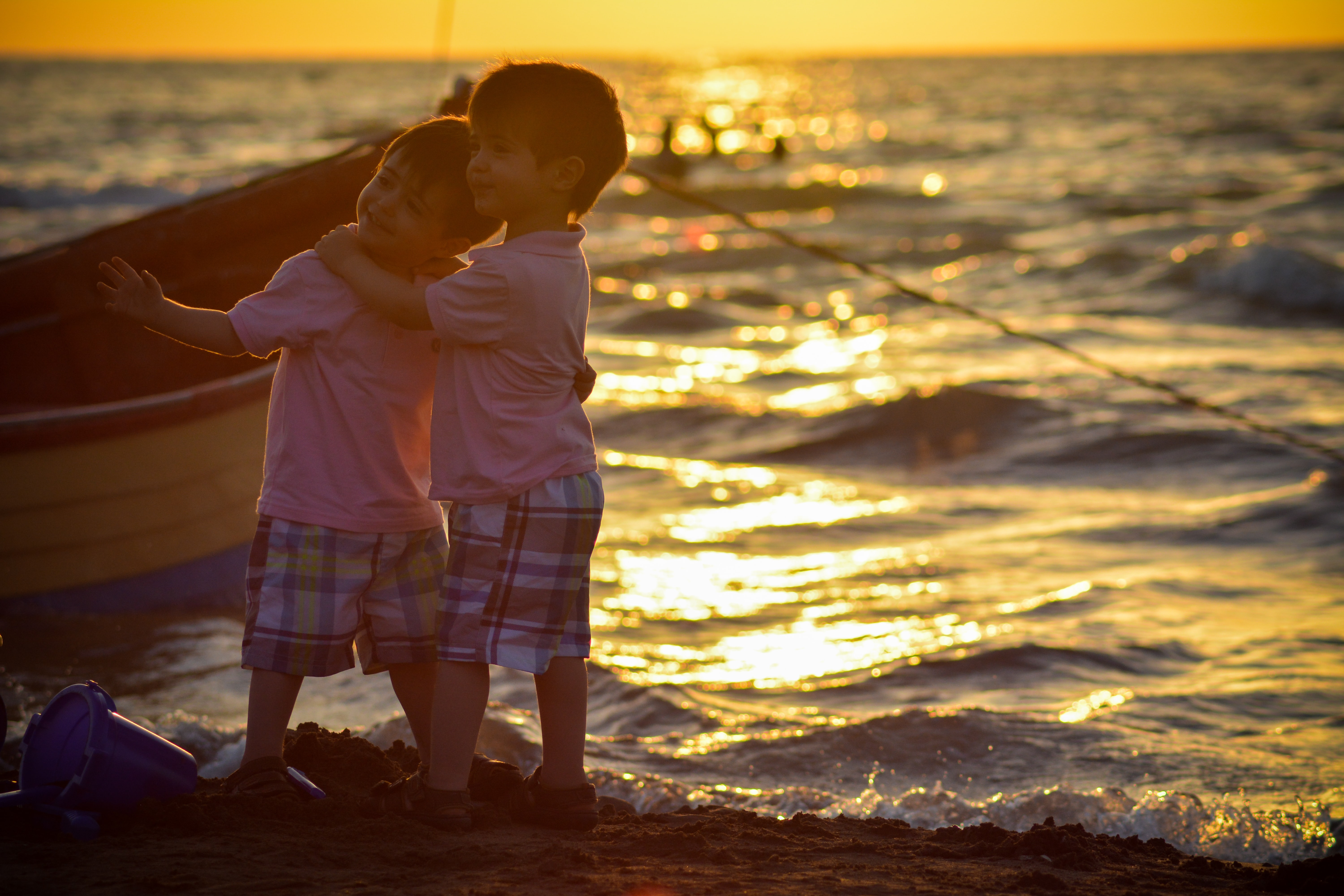 two boys standing on seashore during sunset