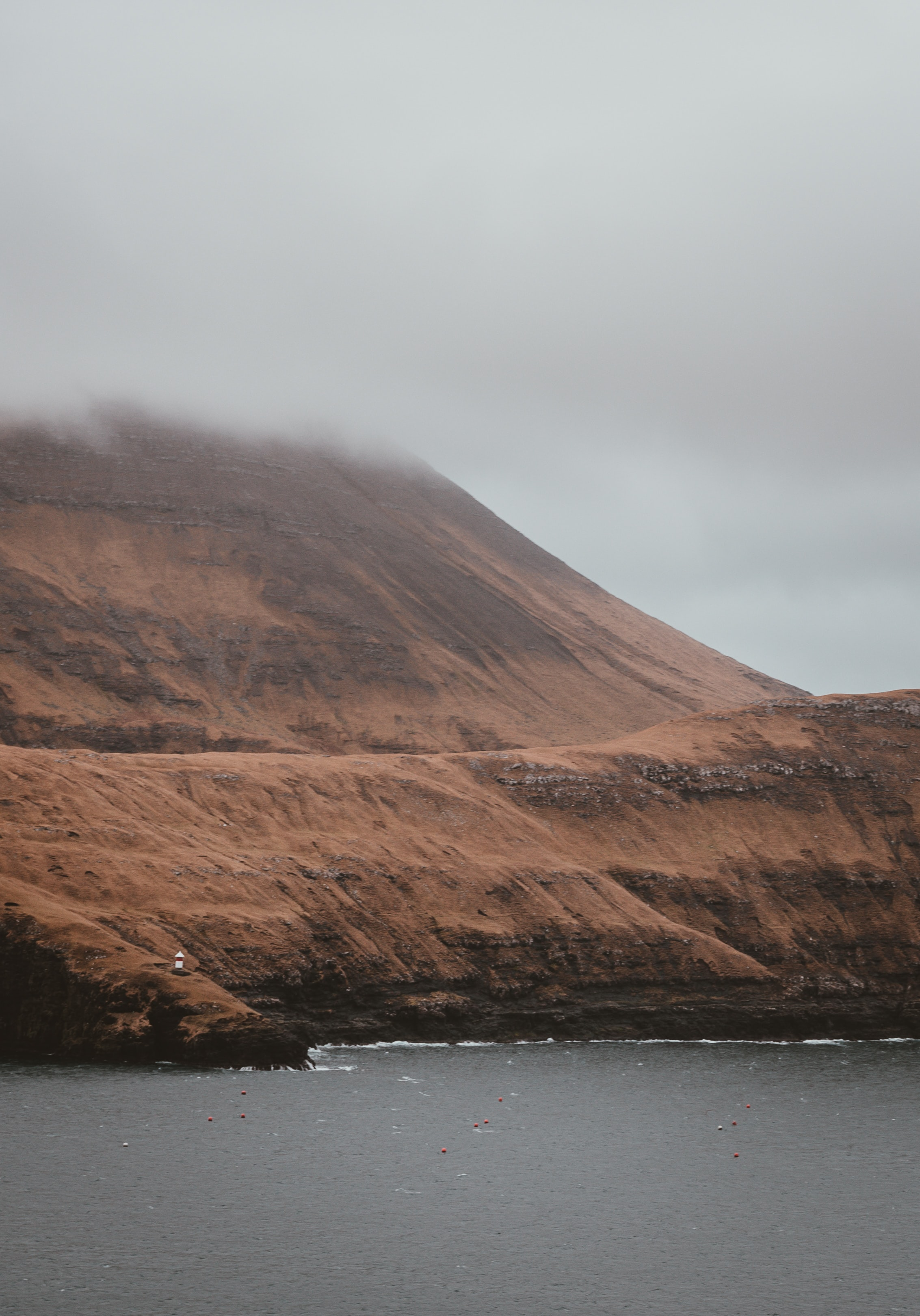 brown mountain near body of water under cloudy sky