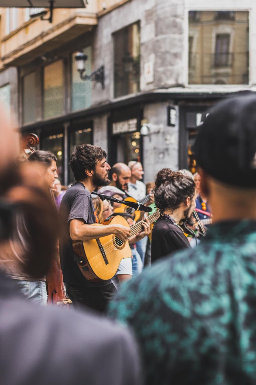 tilt shift photography of man playing guitar