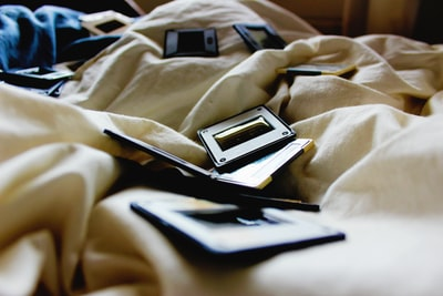 black and brown plastic cases on bed inside room sheet teams background