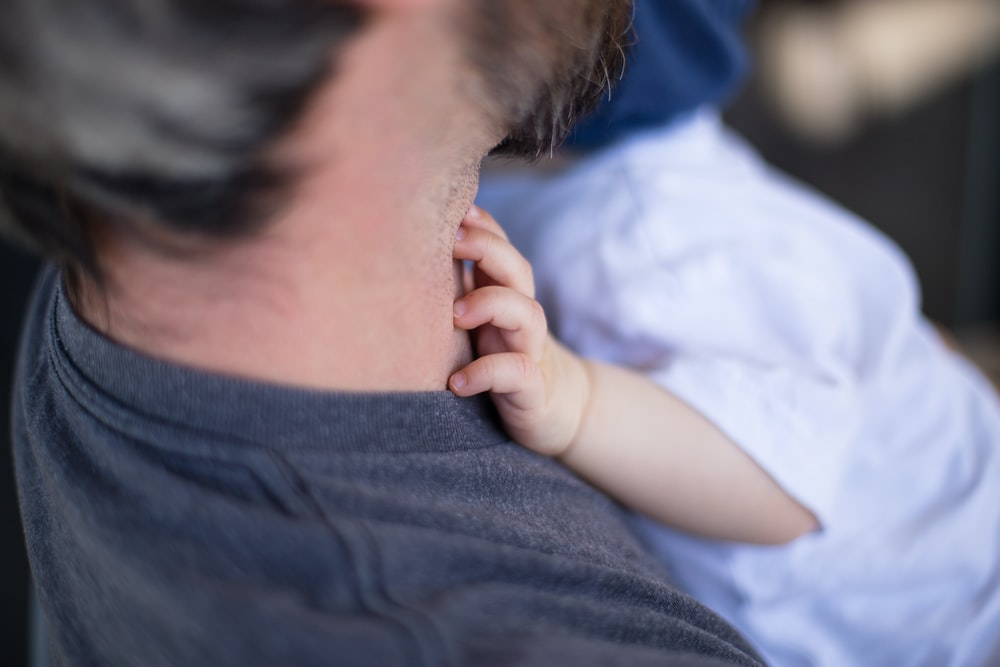 close-up photo of man carrying baby